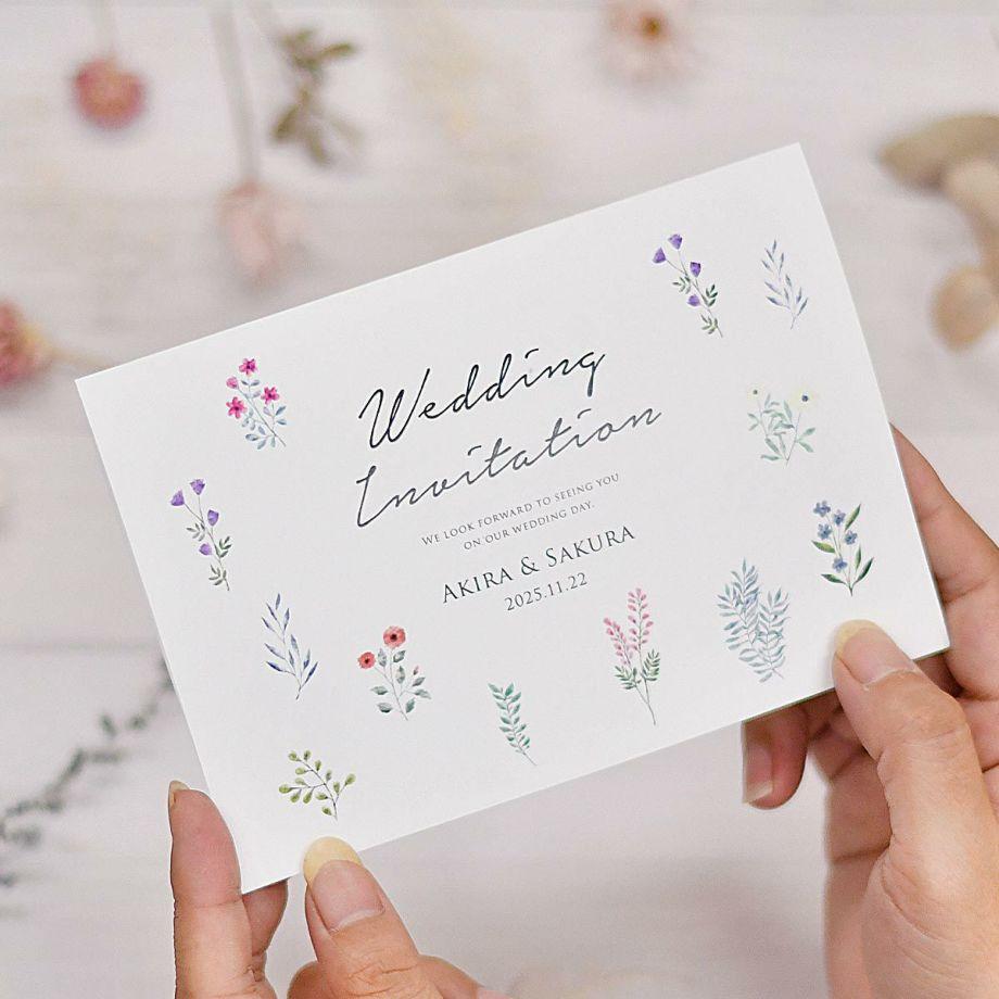 可憐なお花柄が可愛い少人数家族のみ結婚式専用招待状を手で持っている